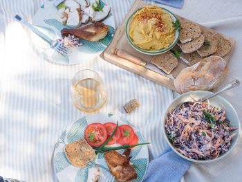 food laid out on a cream picnic blanket with setting for two.