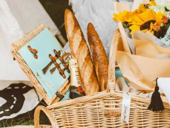 Picnic basket with flowers, baguettes ans champagne.