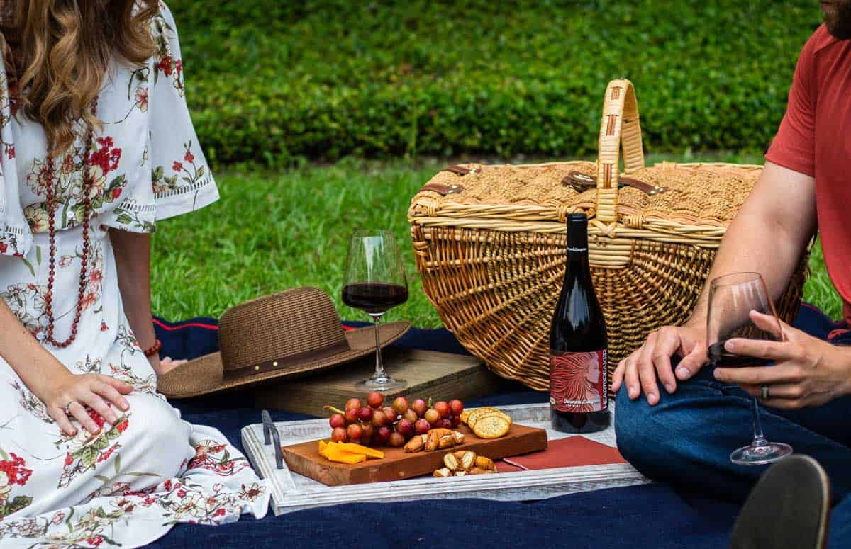 a couple enjoying a picnic on the grass with a classic picnic basket and wine.