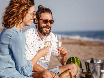 Hip couple enjoying champagne at a beach picnic.