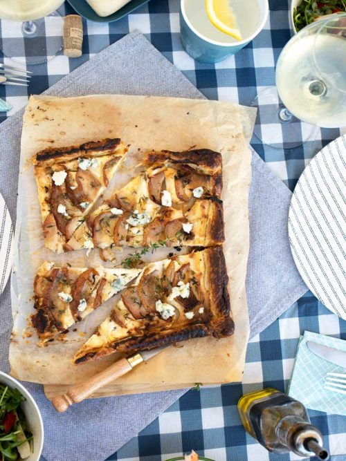Picnic spread on blue and white check tablecloth with a savoury pear tart.